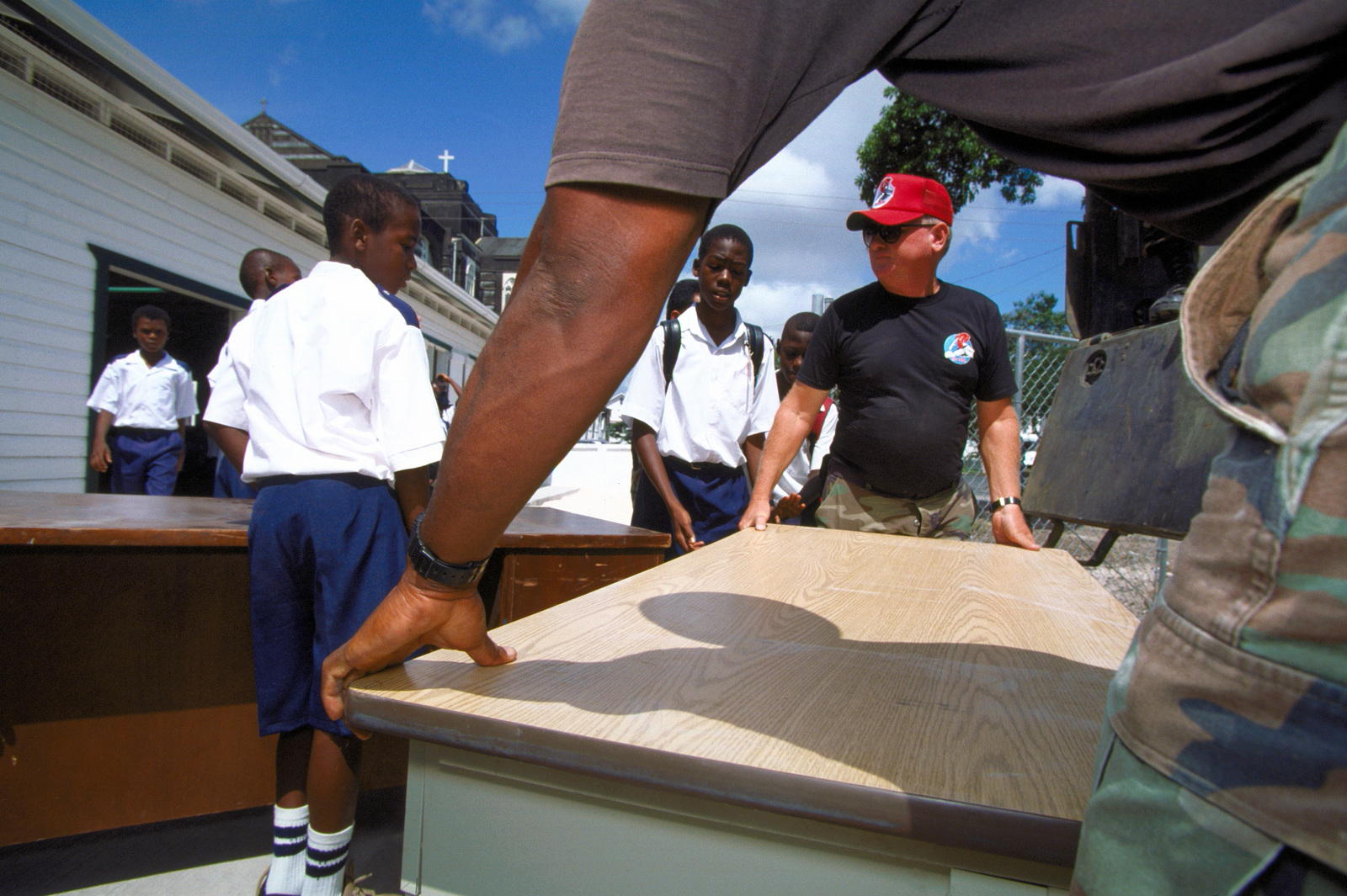 CHIEF MASTER Sergeant Johnson, with the 820th Rapid Engineer Deployment Heavy Operational Repair Squadron Engineer (Red Horse), Nellis Air Force Base, NV helps students carry furniture, donated by Task Force Falcon, into the newly constructed school by the 820th and other the participants of New Horizon '97, first combined humanitarian and civic assistance exercise conducted between the United States and Guyana. Military personnel from the Air Force, Air Force Reserve & National Guard, Army, Army National Guard and Marine Corps participated in the exercise which included engineering and medical readiness training