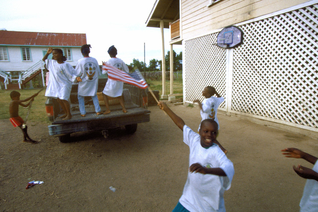 Children who live at the Mahica Children's home, Mahica, celebrate after receiving donated items, such as clothing, foodstuff and money from the men and women of Task Force Falcon deployed to Camp Stephenson. Task Force Falcon personnel were participating in New Horizon '97, first combined humanitarian and civic assistance exercise conducted between the United States and Guyana. Military personnel from the Air Force, Air Force Reserve & National Guard, Army, Army National Guard and Marine Corps participated in the exercise which included engineering and medical readiness training