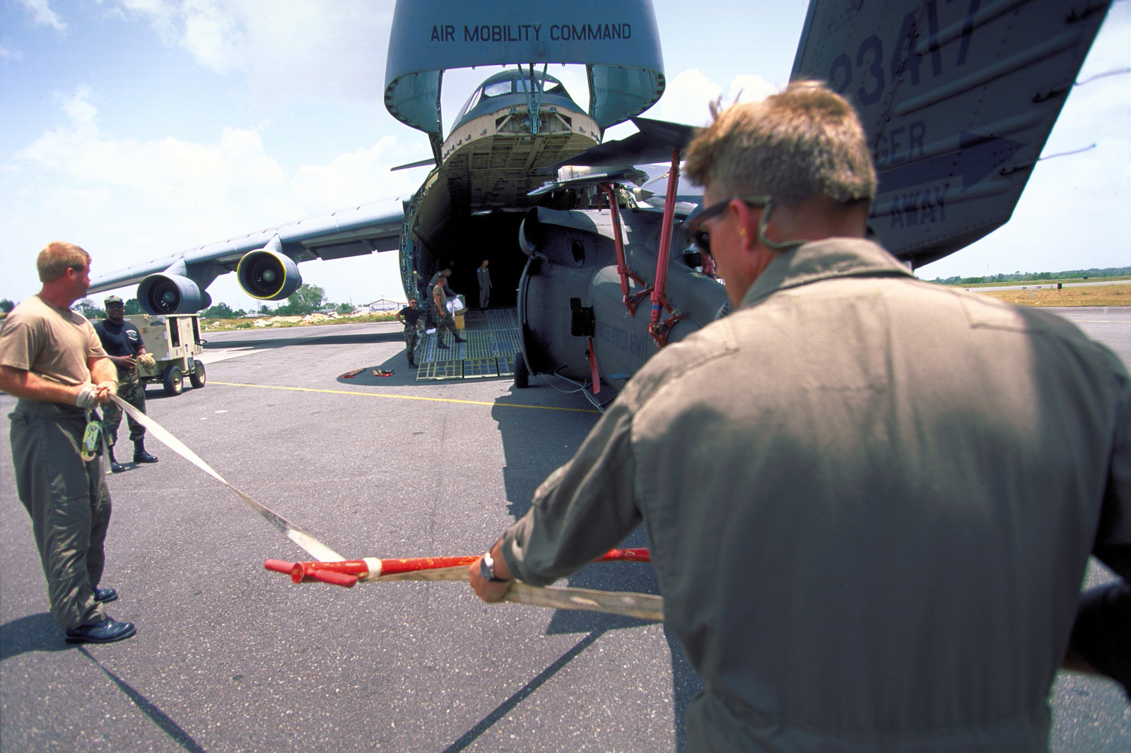 Personnel from ths U.S. Army National Guard's 106th Aviation Unit, Peoria, Ill., prepare to winch one of their UH-60 Black Hawk (Blackhawk) helicopters into C-5 Galaxy cargo bay at Cheddi Jagan International Airport, Timehri, Guyana, for air shipment back to their home base. The 106th participated in the first combined humanitarian and civic assistance exercise conducted between the United States and Guyana. Military personnel from Air Force, Air Force Reserve & National Guard, Army, Army National Guard and Marine Corps participated in the exercise which included engineering and medical readiness training