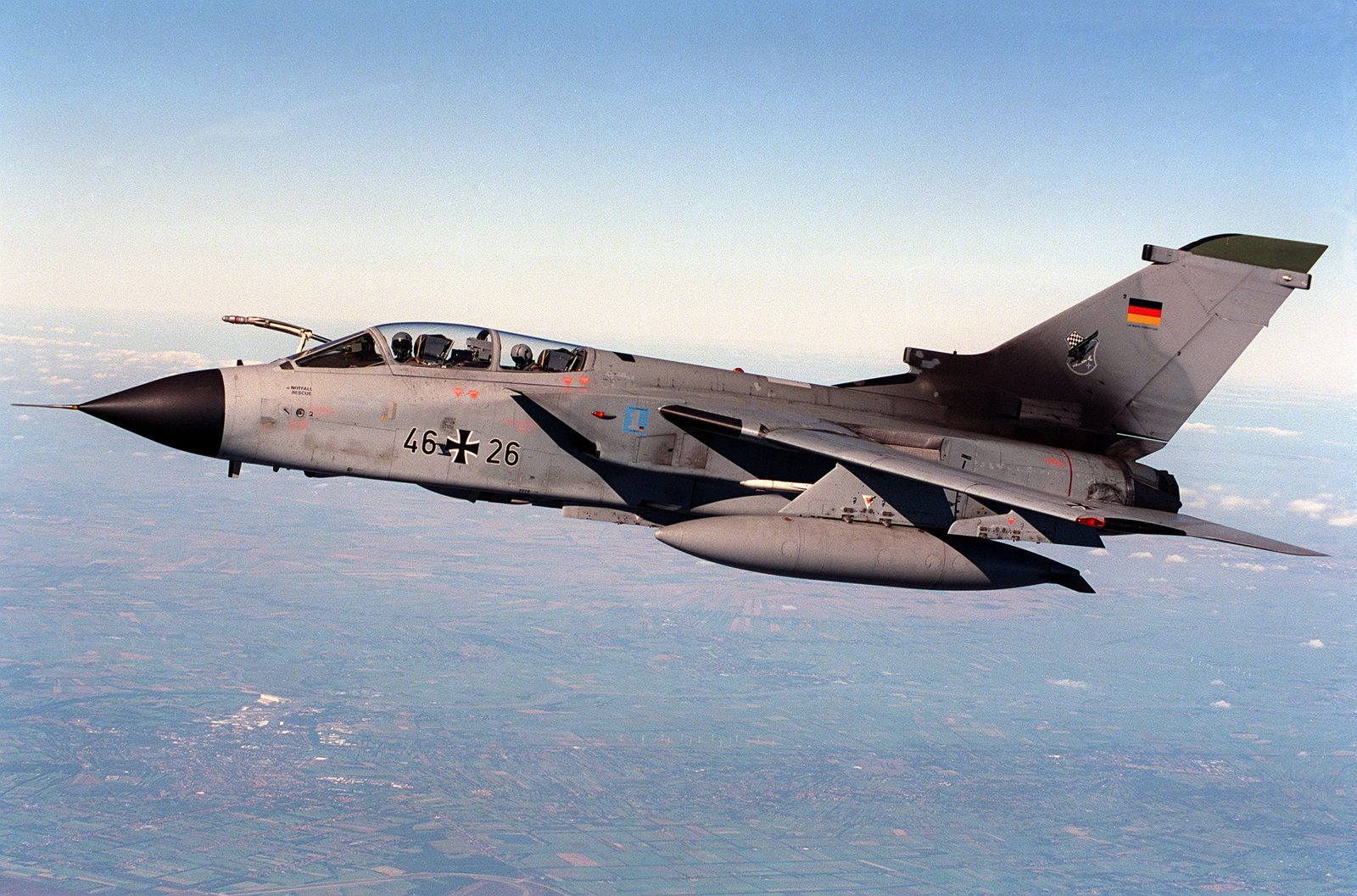 A German GR1 Tornado high speed attack aircraft flies just forward of the right wing of a U.S. Air Force KC-135R tanker, waiting it's turn to be refueled