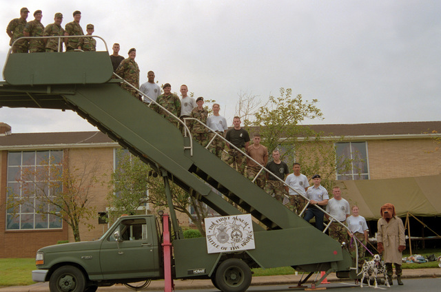 Participants in the 1ST Annual Battle of the Badges fire competition pause for a group photo on a self-propelled passenger stairway. In descending order is SMSGT Darryl Lopes, SMSGT Steven Summer, MAJ Carlon, LT James Bondine, LTC K.C. McClain, unknown, A1C James Johnson, unknown, SRA David Olson, SRA Michelle Graves, unknown, AMN Daniel Bedregal, A1C Brad Hummel, A1C Zaldy Dispo, SRA Robert McKinnly, A1C Scott Tarwater, A1C Summer Barber, A1C Spot (firehouse mascot), McGruff the Crime Fighter Dog (A1C Juan Perez)