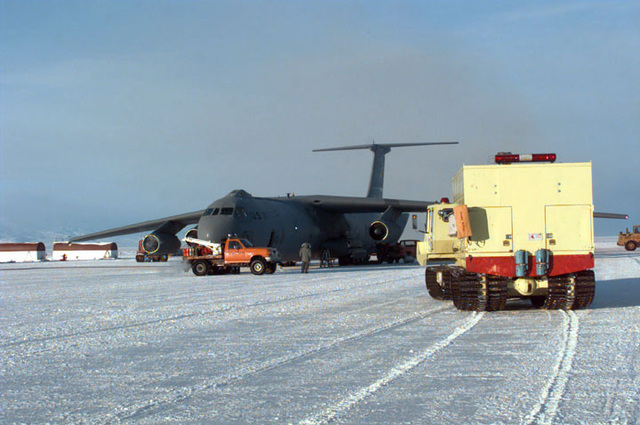 A yellow fire truck stands by as the C-141 Starlifter assigned to the 8th Airlift Squadron (AS), 62nd Airlift Wing, McChord Air Force Base, Washington, sitting on the six foot thick ice runway, is offloaded of its cargo. A truck that pumps hot air into the aircraft sits next to the nose of the C-141. The 8th AS is deployed to support the joint, U.S. Armed Forces and New Zealand Defense Force, military operation which provides logistic support to the U.S. National Science Foundation's Program on Antarctica. SCREEN RESOLUTION ONLY