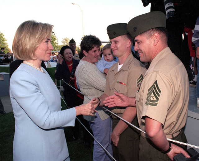 First Lady Hillary Rodham Clinton extends her hand to GUNNERY SGT. Baca. SGT. Liniham looks on