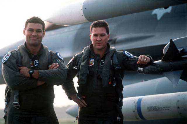 """Two unidentified US Air Force Pilots stand next to a F-16 Falcon, Block 52 aircraft (the only such aircraft in the Air National Guard) from the 157th Fighter Squadron and assigned to the 169th Fighter Wing at McEntire Air National Guard Station, South Carolina. Lans Stout (Not shown), a visiting free-lance photographer from Atlantic Beach, Florida, captures pure beauty in flight (OCT 97). This photo was used for a picture story in the popular """"Code One"""" magazine"""