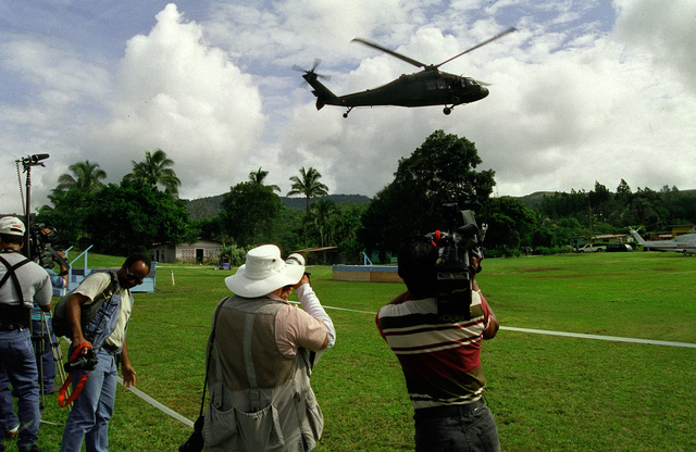 The Panamanian Press and the American Press waits for the First Lady, Mrs. Hillary Rodham-Clinton, to land in the UH-60 Black Hawk (Blackhawk) to tour the Panamanian village of Chica