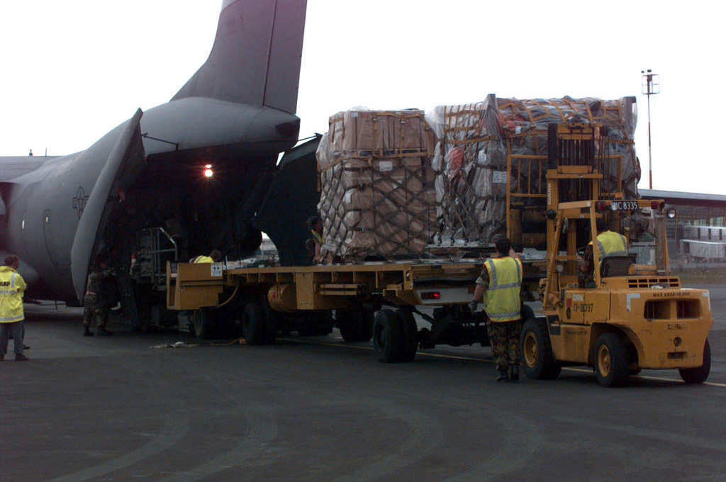 On the airport ramp a K-loader is moved into position to load supply cargo pallets into the rear cargo entrance of the McChord Air Force Base, Washington 62nd Airlift Wing's C-141B Starlifter. Royal New Zealand Air Force members assist in the loading of the Antarctic-bound supplies. The 62nd AW men and equipment are participating in the joint, U.S. Armed Forces and New Zealand Defense Force, military operation which provides logistic support to the U.S. National Science Foundation's Program on Antarctica