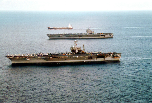 Steaming along an unidentified tanker, U.S. Navy aircraft carriers USS JOHN F. KENNEDY (CV 67) and USS GEORGE WASHINGTON (CVN 73) conduct an underway turnover. John Kennedy will return to Norfolk, VA as George Washington heads towards the Mediteranean on a six-month deployment