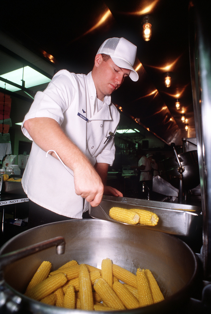 A1C Dale Valensen, 55th Services Squadron food specialist, transfers ears of corn on the cob from a large cooking vat to serving trays in preparation for lunch at the Hillside dining facility