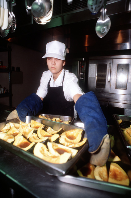 AMN Gina Hillenbrand, 55th Services Squadron food specialist, prepares several large pans of corn squash in preparation for lunch at the Hillside dining facility