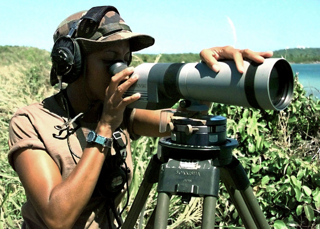 Yeoman SEAMAN Lisa Webb uses a Swarovski AT 80 spotting scope mounted on a tripod to keep an eye out for activities during the joint military exercise GLOBAL GUARDIAN '98