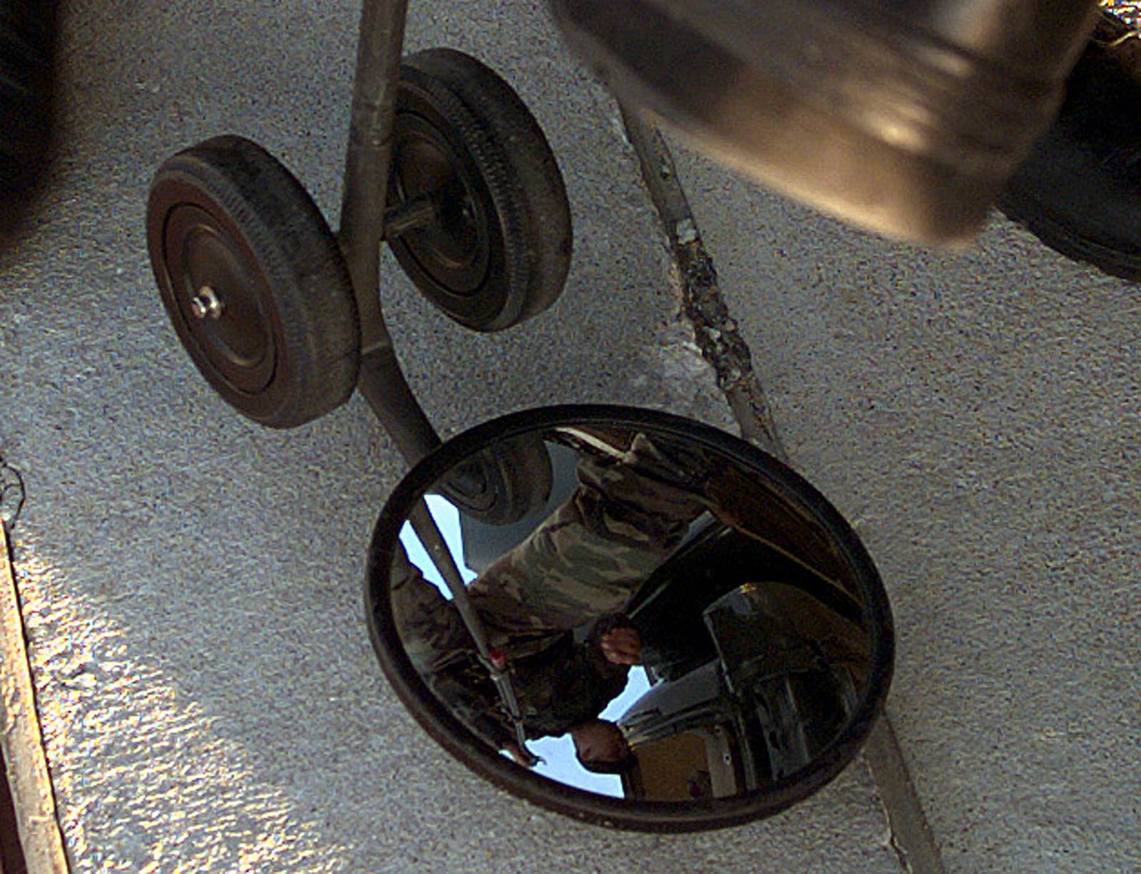 A reflection of a member of the 509th Security Forces can be seen in the under-vehicle mirror used to check the underside of vehicles entering and leaving the priority A area in which B-2 bombers are parked during the joint military exercise GLOBAL GUARDIAN '98