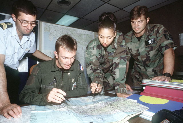 TECH. SGT. Jeff Haynes (right) and AIRMAN 1ST Class Kathleen Teal-Serrano plot a Bosnian flight with French CAPT. Daniel Arnaud and SGT Therry Saludas at San Vito Air Station. San Vito AS, which was officially closed in October 1994, is used to support troops deployed to Bosnia-Herzegovina and aircrews monitoring a no-fly zone above that volatile country. The 352nd Special Operations Group, RAF Mildenhall, England and the 16th Special Operations Wing, Hurlburt Field, Fla. France's Armee de L'Air (air force) and a few U.S. soldiers and sailors comprise most of the joint task force. Exact Date Shot Unknown . Published in AIRMAN Magazine November 1997