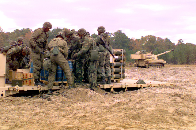 A crew from the 1/41st Field Artillery Battalion prepares ammunition. A M109A6 Paladin 155mm self-propelled howitzer stands in the background