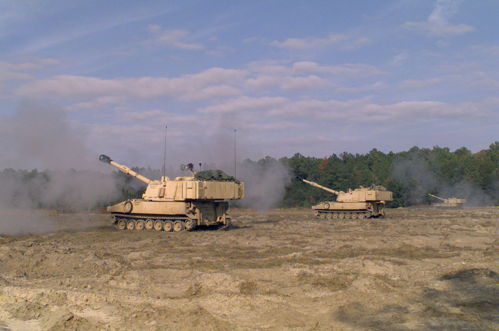 Right side view of several M109A6 Paladin 155mm self-propelled howitzers firing down range