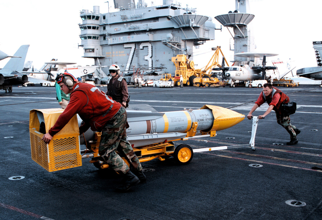 Aviation Ordananceman 3rd Class Brian Skvoretz and Aviation Ordananceman PO3 Robert Alverson move an AIM-54C Phoenix long range air-to-air missile across the flight deck during preparations for flight operations aboard USS GEORGE WASHINGTON (CVN 73). George Washington is in the Persian Gulf to provide forward presence following Iraqs refusal to comply with UN weapons inspections