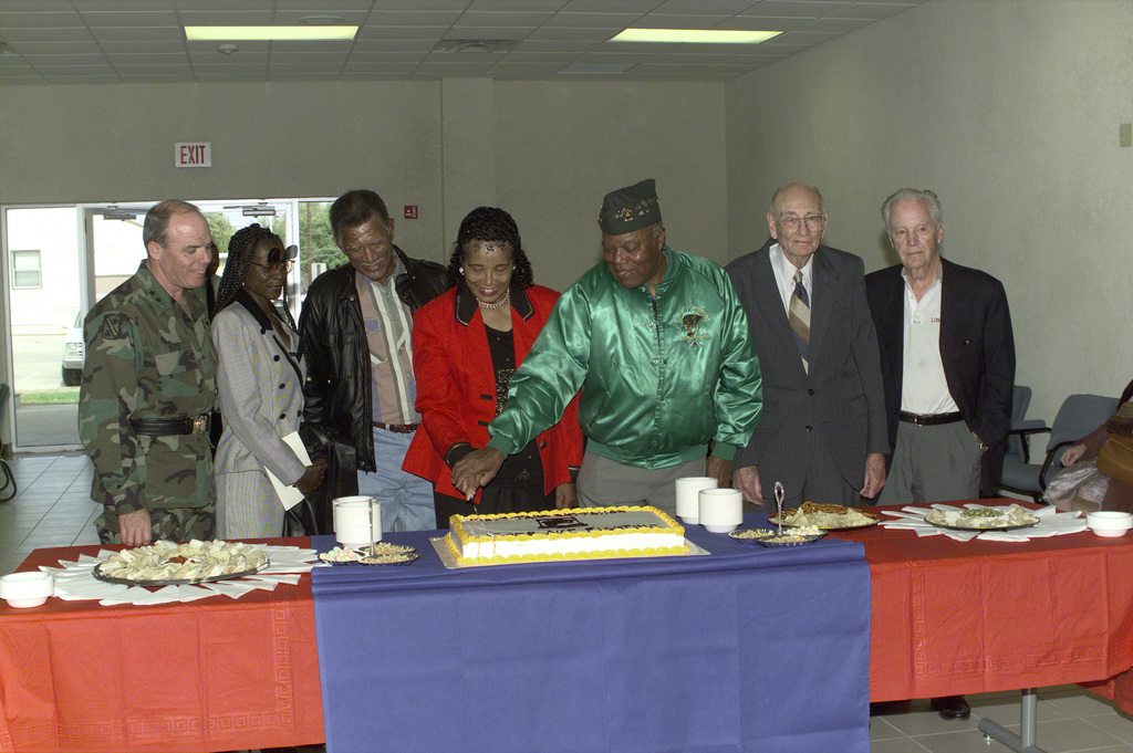 Mrs. Rivers and guests cut the cake at the rededication ceremony of building 121 in memory of SSGT Ruben Rivers, A Co., 761st Tank Battalion, who was awarded the Medal of Honor