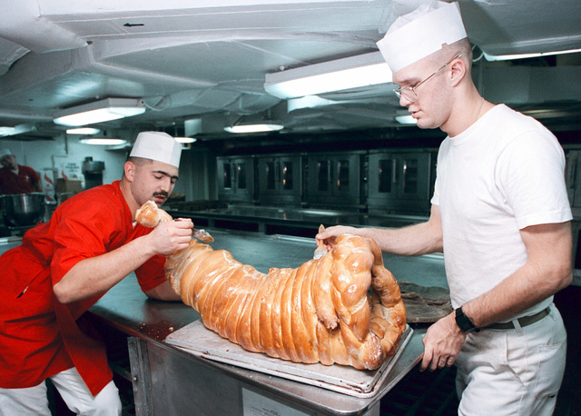 On board the nuclear powered aircraft carrier USS George Washington (CVN 73). US Marine Corps Sergeant Phillip Young (right) and U.S. Navy Mess SPECIALIST Second Class (MS2) William Deese (left) glaze a baked cornucopia during ongoing preparations for a traditional Thanksgiving Day feast. The GEORGE WASHINGTON and her embarked Carrier Air Wing One (CVW-1) are currently operating in the Persian Gulf to enforce UN sanctions against Iraq, by patrolling the no-fly zone. Operation SOUTHERN WATCH, 26 November 1997