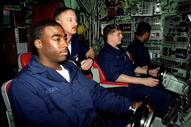 Helmsman of the Watch Fireman Apprentice Darrell Rogers (left) Diving Officer of the Watch Machinist Mate CHIEF (center) and Planesman of the Watch Yeoman 3rd Class Rocky Bolin (center right) comprise the boats steering team as they maneuver the nuclear powered fast attack submarine USS ANNAPOLIS (SSN 760). Annapolis is operating in the Persian Gulf as part of the aircraft carrier USS GEORGE WASHINGTON (CVN 73) battle group and is enforcing UN sanctions against Iraq in support of operation Southern Watch