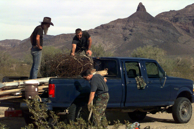 A Cabeza Prieta National Refuge environmentalists (Left) assists US Air Force Technical Sergeant Crider and Lieutenant Hyden in collecting darts and excess material from the refuge. The Air Force is exploring methods to remove jettisoned training darts in an effort to restore wilderness qualities in the refuge