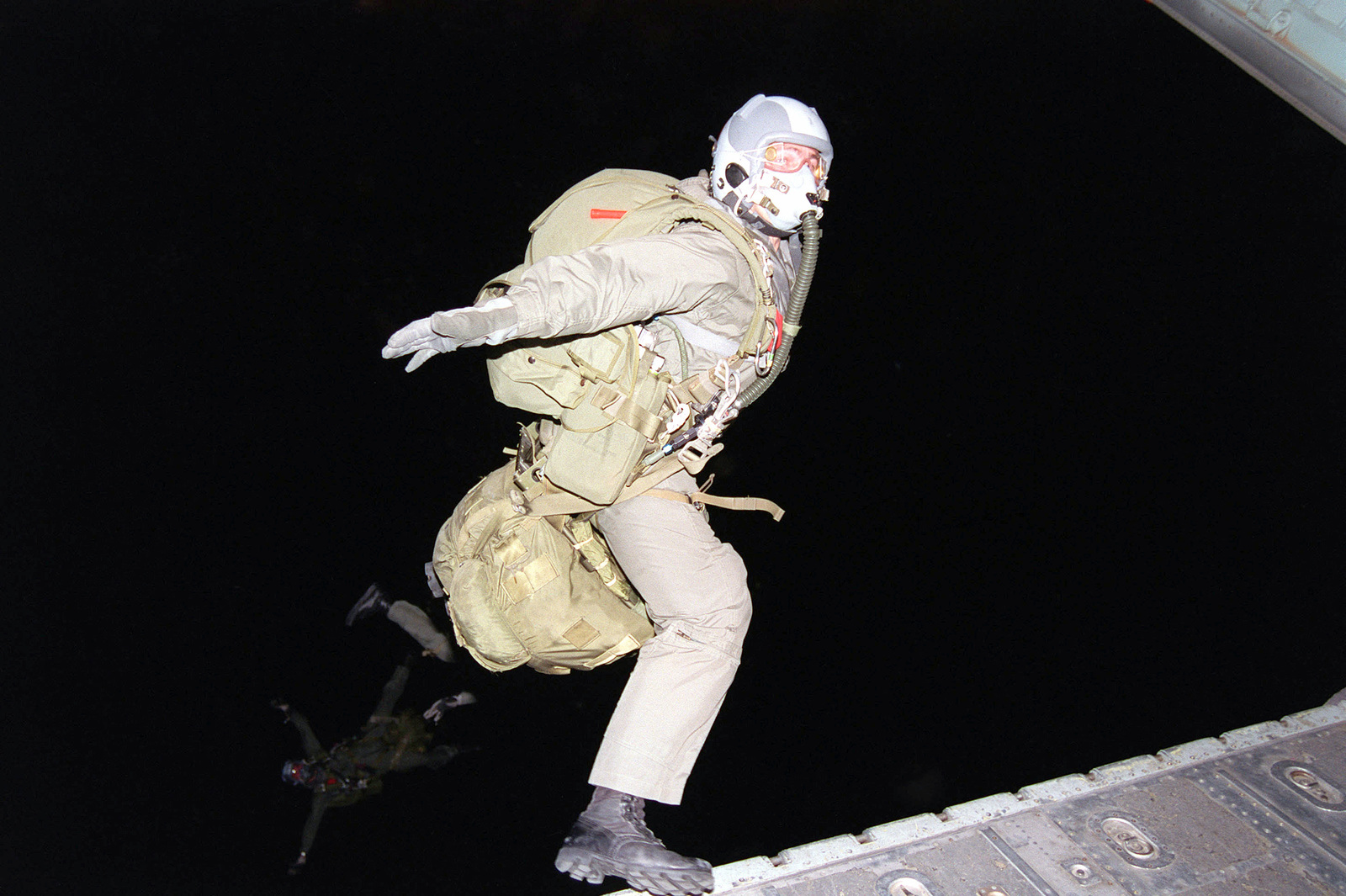 SPECIALIST First Class Brad Beauchamp, a jumpmaster from A Company, 2nd Battalion, 3rd Special Forces Group, Fort Bragg, North Carolina, performs a pivot poised exit on a night jump with oxygen and equipment, at 25,000 feet above Roosevelt Roads Naval Air Station, Puerto Rico