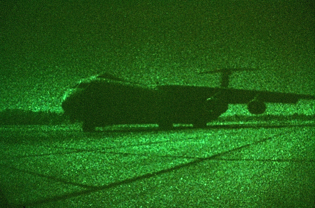 A Special Operations Low Level (SOLL II) C-141B Starlifter, about to take-off from a moonlit airstrip. With the use of night vision goggles, special lighting fixtures, and constant training, aircrew of the 16th Special Operations Squadron, Charleston, South Carolina, see with near conventional light illumination (i.e landing lights, flightdeck instrumentation, cargo compartment lighting, and etc.)