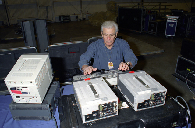 US Air Force (USAFR) MASTER Sergeant (MSGT) MAC McEachern, assigned to the Video Documentation Team, set up monitoring equipment for the US Air Force in Europe (USAFE) Band before a performance during an Operation SEASONS GREETINGS '97 concert held at Aviano Air Base, Italy