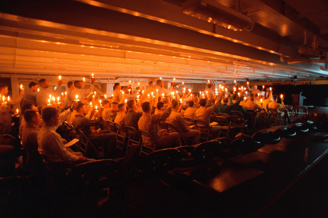 Crew members celebrate a traditional candle light service on board the USS GEORGE WASHINGTON (CVN 73) during religious services Christmas Eve, 1997. George Washington and Carrier Air Wing One are operating in the Persian Gulf to enforce UN sanctions against Iraq, under operation Southern Watch
