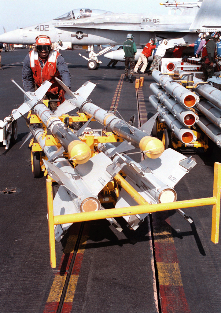 Aviation Ordnanceman AIRMAN Derrick Coach moves AIM-9 Sidewinder missiles across the flight deck of the aircraft carrier USS GEORGE WASHINGTON (CVN 73). George Washington is deployed to the Persian Gulf in support Operation Southern Watch