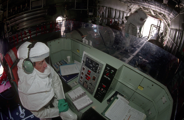 MASTER Sergeant (MSGT) Bill Rooks, monitors the spray control panel aboard a C-130 Hercules with the 910th Airlift Wing, while dangerous pesticides are loaded aboard for a spray mission