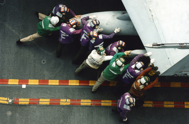 Military Photographer of the Year Winner 1998 Title: First Launch Category: Feature Place: Honorable Mention FeatureFlight deck personnel push the wing of a F-18 Hornet so it can be taken down to the hangar deck. The F-18 Hornet was part of NATC PAX RIVER taking part of the flight deck certification of the USS Harry S. Truman (CVN-75)