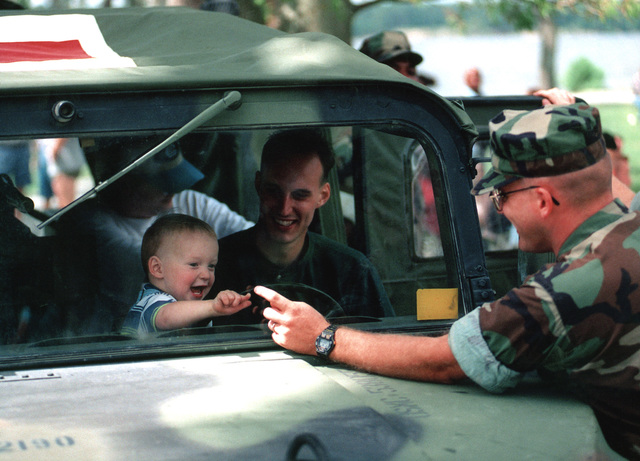 Military Photographer of the Year Winner 1998 Title: N/A Category: Feature Place: Honorable Mention FeatureA U.S. Naval Corpsman of 2D Light Armored Reconnaissance Battalion plays a fun game with a little boy through the windshield of his Hummvee while the boy's father looks on during 2D Light Armored Reconnaissance Battalion's family day '98 at Camp Lejeune, North Carolina