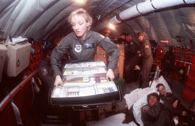 STAFF Sergeant Theresa Wagner prepares a medical kit for patients, during an in-flight drill. Patients in the background are (left to right), MASTER Sergeant Mahoney and Captain Edgeman. SSGT Wagner, MSGT Mahoney and CPT Edgeman are all stationed with the 452nd Aeromedical Evacuation Squadron, March Air Reserve Base, California
