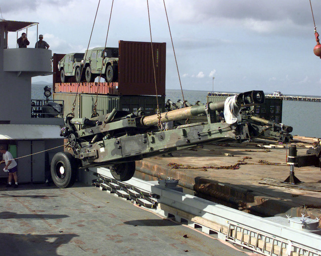 An M-198 155mm howitzer is loaded onto a YFU-81 harbor utility craft by a crane prior to it being transported to Vieques Island, Puerto Rico for PURPLE DRAGON, a joint exercise involving B Battery, 1ST Battalion, 377th Artillery Regiment (Air Assault), Fort Bragg, North Carolina, and the 26th Marine Expeditionary Unit, Camp Lejeune