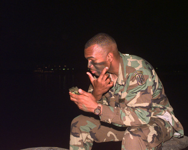SGT Henry Murray of B Battery, 1ST Battalion, 377th Field Artillery Regiment (Air Assault), Fort Bragg, North Carolina, puts on camouflage as his unit prepares to board a ship that will take him to Vieques Island, Puerto Rico for PURPLE DRAGON, a joint exercise with the 26th Marine Expeditionary Unit, Camp Lejeune
