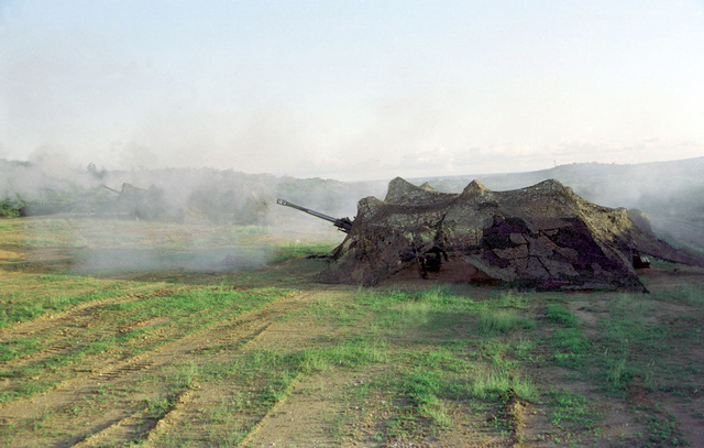 M-198 155mm howitzers, hidden under camouflage netting, from B Battery, 1ST Battalion, 377th Field Artillery Regiment (Air Assault), Fort Bragg, North Carolina, fire from gun position 3 during Supporting Arms Coordination Exercise, JTFX 98-1