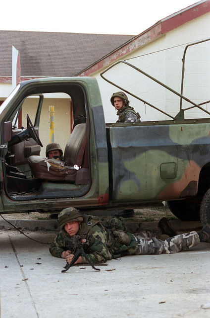 Marines from Charlie Company, 1ST Battalion, 6th Marines, use a broken pickup truck for concealment at the Military Operations in Urban Terrain facility (MOUT) during Urban Warrior. Urban Warrior is the U.S. Marine Corps Warfighting Laboratory's series of limited objective experiments examining new urban tactics and experimental technologies