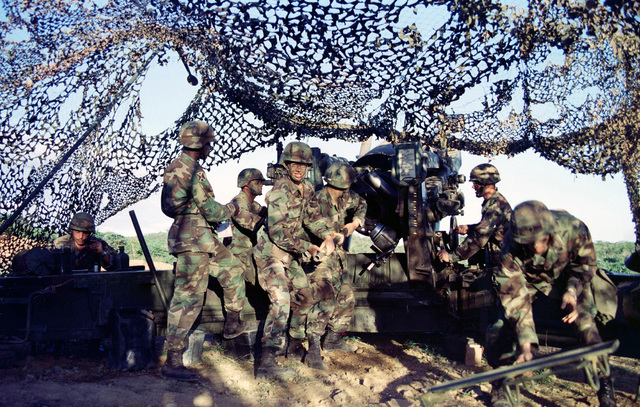 Soldiers from Bravo Company, 1ST Battalion, 377th Infantry Regiment, Fort Bragg, North Carolina, ram a high explosive round into their M-198 Howitzer gun at Gun Position 3, Vieques Island, Puerto Rico, during Supporting Arms Coordination Exercise, Joint Task Force Exercise 98-1. (Substandard image)