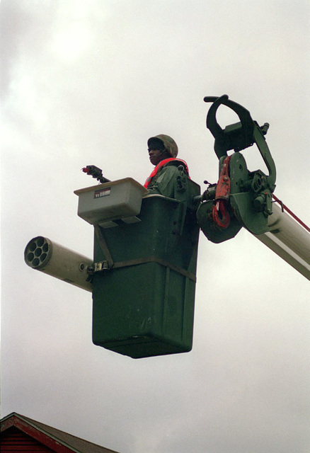 Using a crane bucket to obtain a higher vantage point, a Marine
