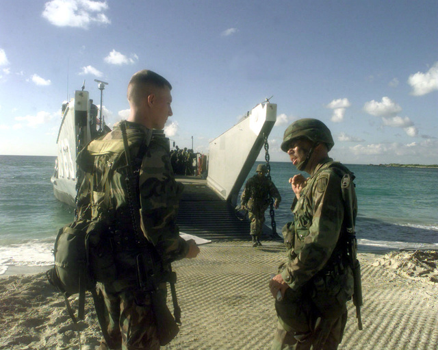 1SG Richard Early (left) of B Battery, 1ST Battalion, 377th Field Artillery Regiment (Air Assault), Fort Bragg, North Carolina, discusses the load plan of the landing craft unit (LCU) with Marine CPL Jason Rea of the 26th Marine Expeditionary Unit, Camp Lejeune, North Carolina regarding the extraction of the soldiers during JTFX 98-1