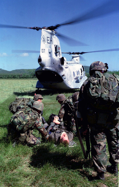 """Marines from Kilo Battery, Battalion Landing Team 3/2 tend to the """"injured"""" pilot after a TRAP (Tactical Rescue of Aircraft and Personnel) mission aboard Vieques Island, Puerto Rico during Joint Task Force Exercise 98-1. A CH-46 Sea Knight helicopter from Helicopter Marine Medium Squadron 264 (attached to the 26th Marine Expeditionary Unit) is in the background"""