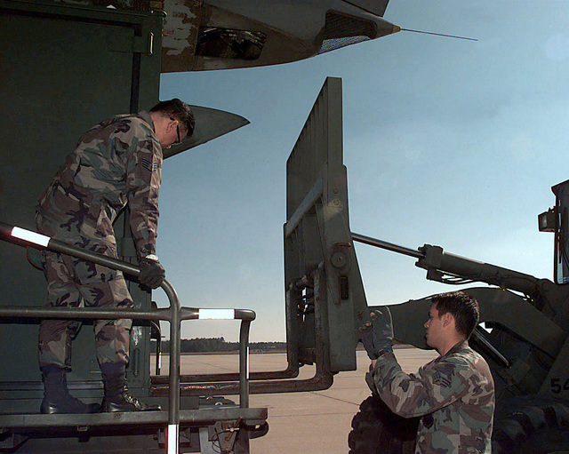 STAFF Sergeant Bud Aretto and SENIOR AIRMAN William Burns, 743rd Maintenance Squadron, Pope Air Force Base, North Carolina, guide a fork lift up to a C-141 Starlifter aircraft from the 621st Air Mobility Operation Squadron, McGuire Air Force Base, New Jersey. The cargo is to be air dropped during Joint Task Force Exercise (JTFX) 98-1 on Fort Bragg, North Carolina