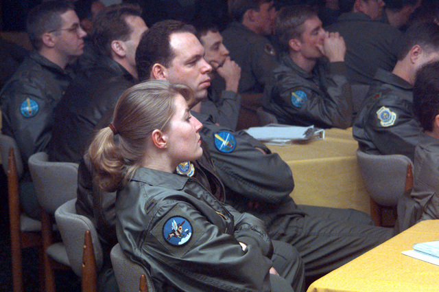 Captain John McGan, 8th Airlift Squadron, McChord Air Force Base, Washington, and 1ST Michelle Welborn, the only female pilot in the excerise, listen to mission briefings the night prior to a troop drop during Joint Task Force Exercise (JTFX) 98-1