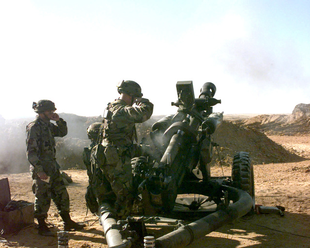 Members of 3rd Section, A Battery, 1ST Battalion, 319th Field Artillery Regiment (Airborne), Fort Bragg, plug their ears as the M119 105mm howitzer fires during a joint field training. The soldiers are wearing MILES (Multiple Integrated Laser Engagement System) equipment. (Duplicate image, see also DASD9901535 or search 980201A6522J506)