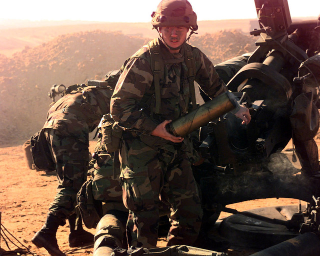 SGT. Jared Reesor, 3rd Section, A Battery, 1ST Battalion, 319th Field Artillery Regiment (Airborne), walks away carrying the empty shell of a 105mm artillery round fired from an M119 Howitzer