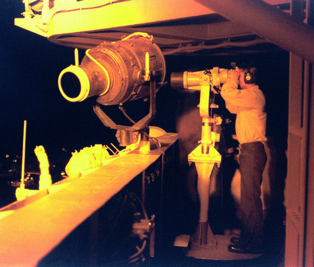 Under the amber lights of the ships superstructure, Signalman 3rd Class Gilbert Kreutzfeld stands a night watch from one of the many look-out stations onboard the aircraft carrier USS INDEPENDENCE (CV 62). Independence and her embarked Carrier Air Wing Five (CVW5) are on deployment in the Persian Gulf in support of operation Southern Watch
