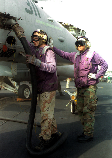 Aviation Boatswains Mate AMN Richard McCulley and Aviation Boatswains Mate 1ST Class Joseph Sumbillo refuel an F/14 Tomcat before it is to be moved to the catapult and launched from the USS INDEPENDENCE(CV 62). INDEPENDENCE is deployed to the Persian Gulf in support of Operation Southern Watch