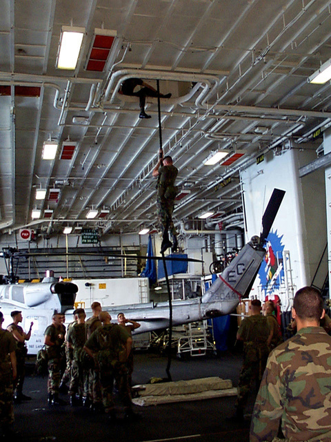 Special Operations Capable Marines from 24th Marine Expeditionary Unit (MEU) aboard USS GUAM (LPH 9) conduct Fast Rope training in the hangar bay. GUAM is in transit to the Persian Gulf in response to a U.S. Central Command request for an increased military presence in the region under Operation Southern Watch