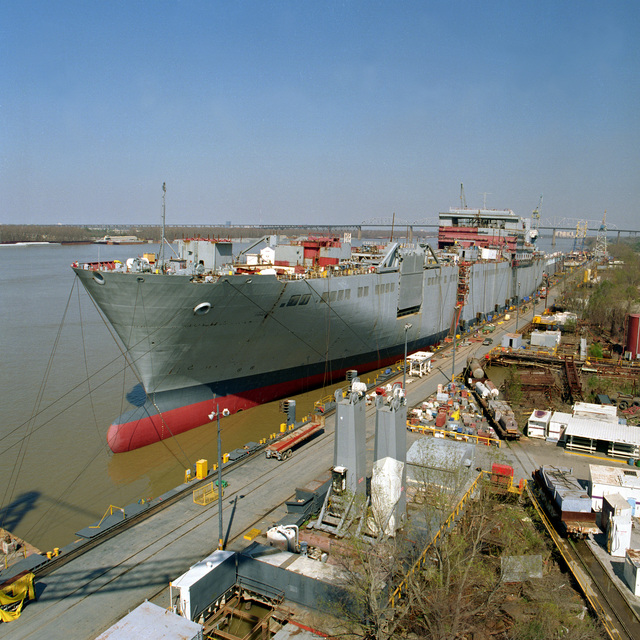Port bow view of the Military Sealift Command (MSC) Bob Hope Class Vehicle Transport Ship USNS FISHER (T-AKR 301) tied up at the fitting out pier at the Avondale Industries, Shipyard Division. This progress photo shows the ship at 80 % completion