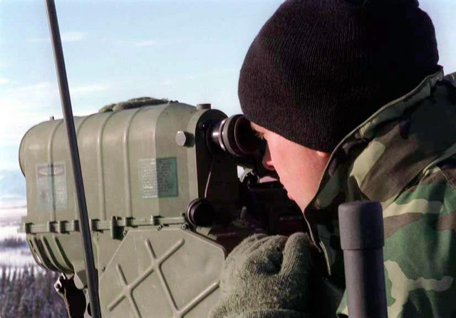 SGT A. McMellan from Communications Company, 1ST Light Armored Reconnaissance Battalion, looks through an AN/PAQ-3 Modular Universal Laser Equipment (MULE) scope that guides aircraft ordnance onto the proper location during the cold weather exercise. (SCREEN RESOLUTION ONLY) (Duplicate image see also DMSD0204651 or search 980221M6225S001)