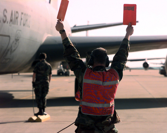 US Air Force STAFF Sergeant Darrell Bramer (Foreground), a Crewcheif with 92nd Aircraft Generation Squadron, Fairchild Air Force Base, Washington, recovers an arriving KC-135 Stratotanker. SSGT Bramer is deployed to Moron Air Base, Spain, in support of Phoneix Duke II